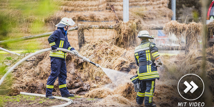 Feuerwehr löscht Strohballen in einer Scheune