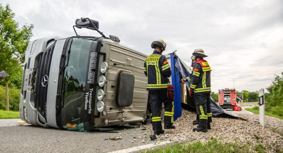 Kieslaster kippt in Autobahnabfahrt auf die Seite